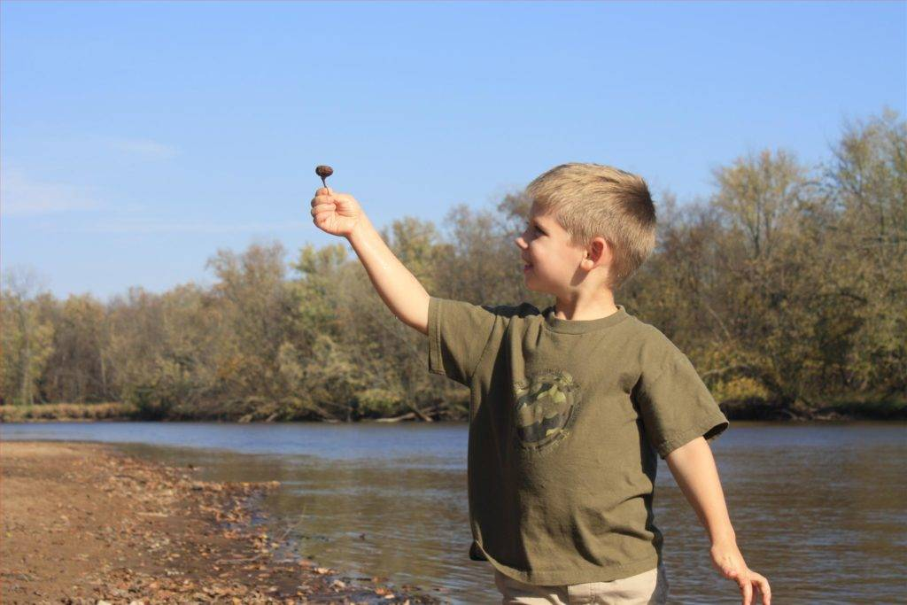 Boy on River Holding Object